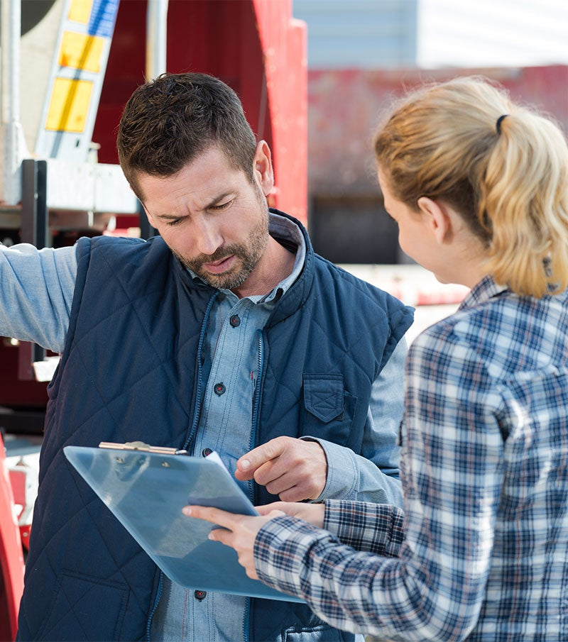 Commercial Truck Driver examining a clipboard